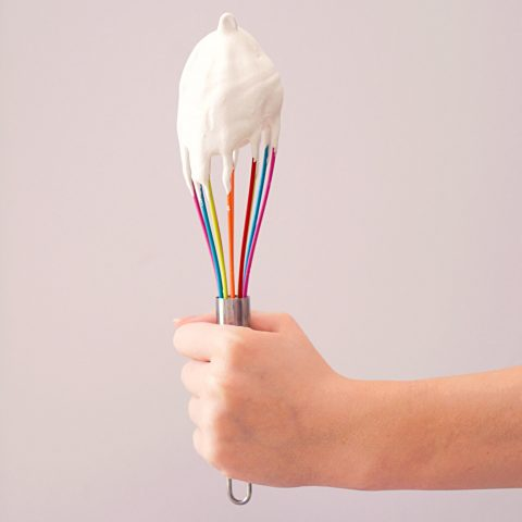 Hand holding whisk covered in meringue
