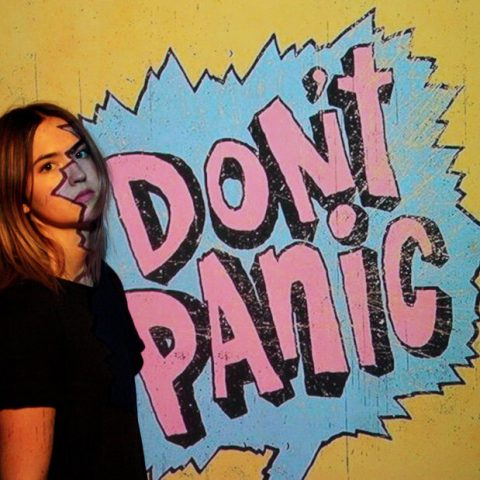 Young person next to a sign saying don't panic