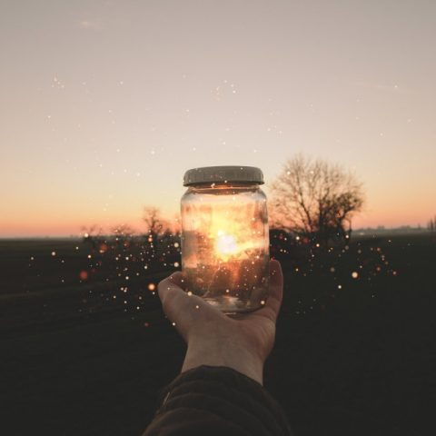 person holding a jar in front of a sunset