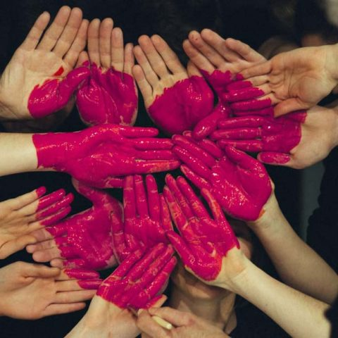 Hands with paint on to form the shape of a heart