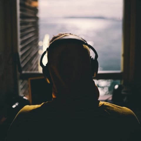 person wearing headphones staring out a window