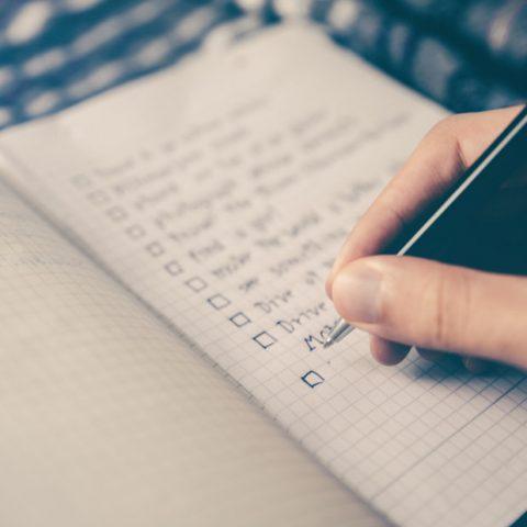 person writing checkbox list