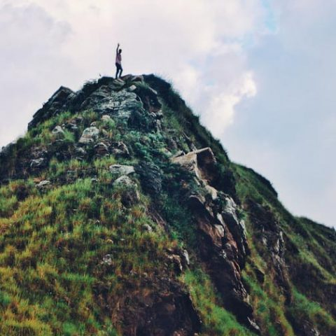 Person on top of a mountain waving