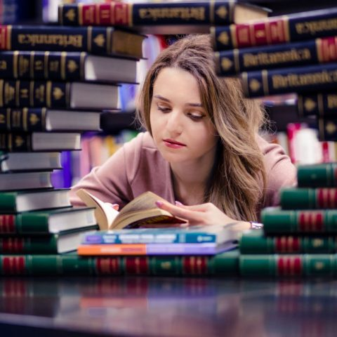 young person doing work between stacks of books