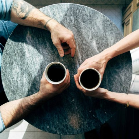 two people at a table drinking coffee