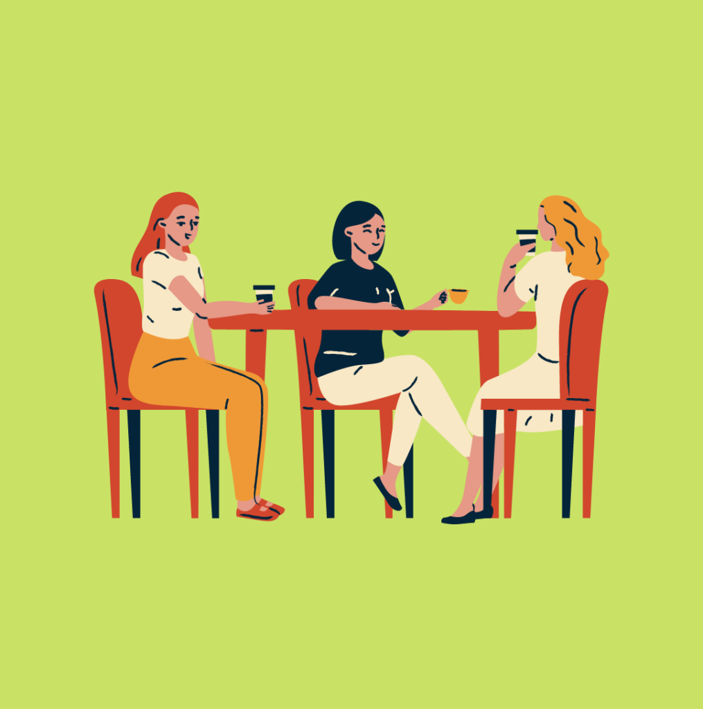 Three people sitting at a table talking and having coffee together